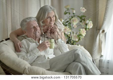 Two elderly people sitting near couch with tea