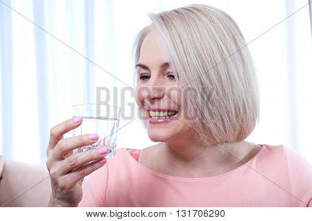 Portrait beautiful middle aged woman drinking water in the morning. Woman's face close up