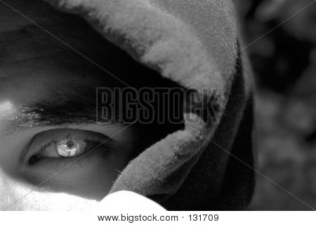 a hooded figure with a bright eye poster