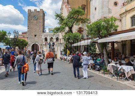 TAORMINA ITALY - MAY 21: Tourists walking along several restaurants at the main plaza of Taormina on May 21 2016 at the island Sicily Italy