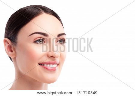 Portrait of beautiful young woman with healthy complexion. She is looking forward and smiling happily. Isolated and copy space in right side