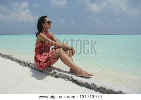 Tanned girl with dark hair in red pareo in the Maldivian beach