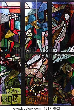 KLEINOSTHEIM, GERMANY - JUNE 08: 11th Stations of the Cross, Crucifixion: Jesus is nailed to the cross, stained glass window in Saint Lawrence church in Kleinostheim, Germany on June 08, 2015.