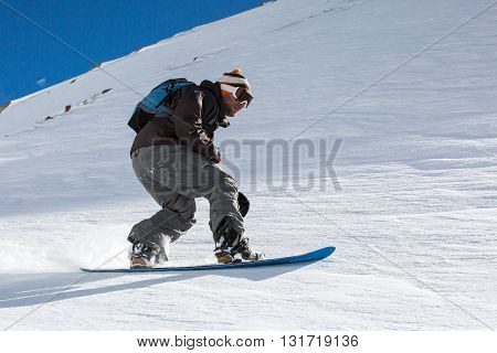 Man Snowboarder Snowboarding On Fresh White Snow On Ski Slope On Sunny Winter Day