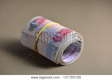 UAE dirham currency notes rolled and tied with rubber band.