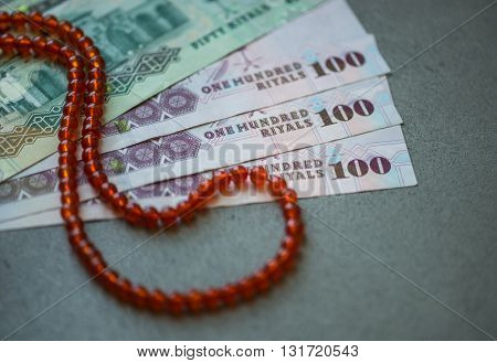 Saudi Riyal currency notes and Islamic prayer beads. Sharia'h or Islamic banking.