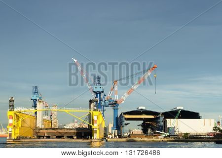 KAOHSIUNG TAIWAN -- AUGUST 12 2015: A floating dry dock is surrounded by construction cranes in the wharf area of Kaohsiung Port.