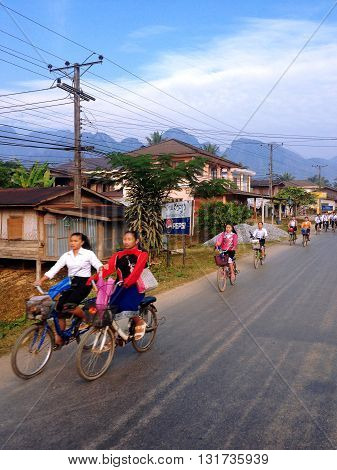 VANG VIENG LAOS - December 09 2013 : Students cycling go to school on in Vang Vieng Laos. Around the villages there are more kids than adults.