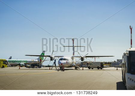 HERAKLION GREECE - APRIL 28 2016: Pre-flight preparation. Mechanic serves two engine-propeller civilian aircraft at Heraklion Airport N. Kazantzakis Crete Greece