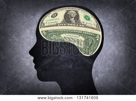 Silhouette of human head with dollar bills inside instead of the brain