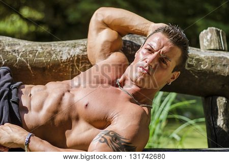 Handsome, serious muscleman leaning on wood bench outdoor, shirtless