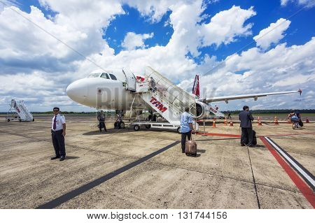 Foz do Iguacu, Brazil - December 9, 2015: Passengers boarding Tam Airlines Airbus 320 airplane at Cataratas International Airport in Foz do Iguacu, Parana, Brazil. TAM is the Brazilian brand of Latam Airlines and the largest Brazilian airline.