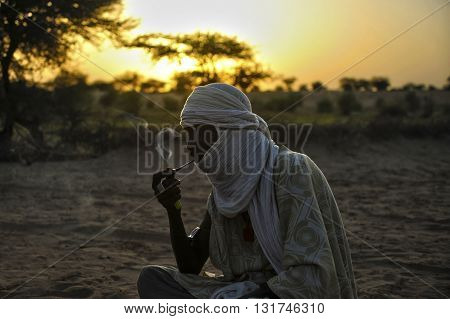 TIMBUKTU, MALI, 02-SEPTEMBER-2011. Tuareg smoking his pipe in camp near the city of Timbuktu
