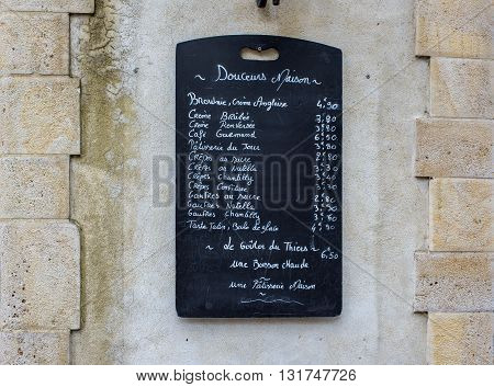 Saint-Jean de Luz France - May 21 2016: Creperie menu blackboard on a stone wall in a street of Saint-Jean de Luz. Aquitaine France.