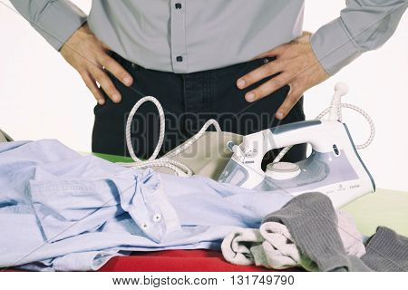 Man trying to iron clothes but has difficulty