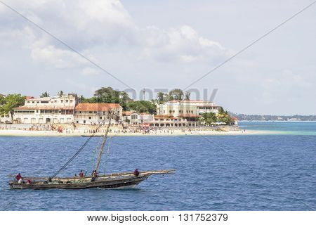 Traditional Dhow Boat Traveling Along The Coast Of Zanzibar