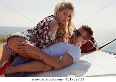 love story. fashion outdoor photo of impassioned couple in casual clothes, posing beside luxurious car poster