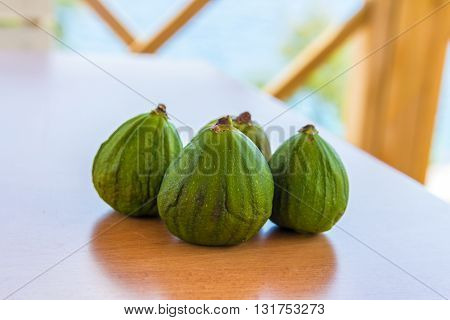 three green figs on a wooden table
