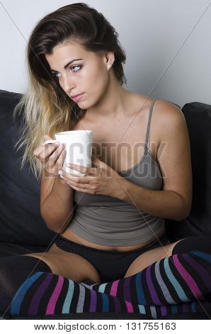 Young Pretty Girl With Cup Of Coffee Sitting In Armchair