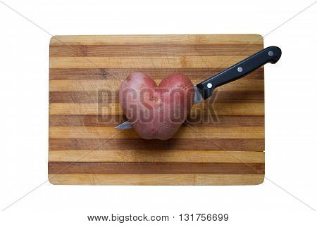 horizontal top view of a heart shaped potato on a wood cutting board with a kitchen knife going through it