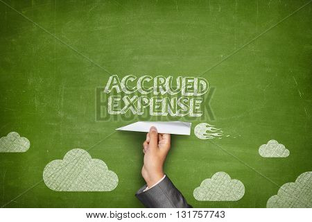 Accrued expense concept on black blackboard with businessman hand holding paper plane
