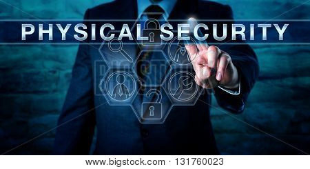 Intelligence officer is pushing PHYSICAL SECURITY on an interactive transparent control screen. Business metaphor and technology concept. Application icons with security tools arranged in a cycle.