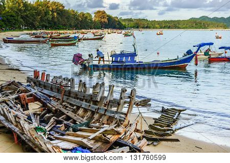 Phuket Thailand - November 19 2012: Boat wreck on beach & traditional long-tail & speed boats used for tourist & fishing trips moored in bay. Two boatmen board long-tail boat for trip. Rawai beach on southern tip of Phuket southern Thailand