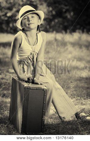 Cute little boy sitting on a big suitcase. Retro style.