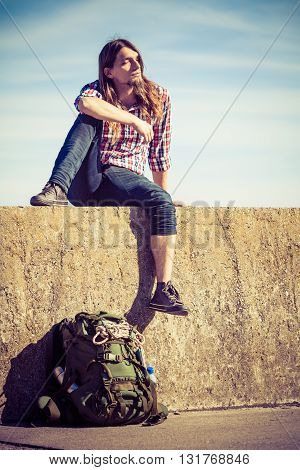 Man tourist backpacker relaxing outdoor sitting on grunge wall against sky. Adventure summer tourism active lifestyle. Young hipster guy tramping