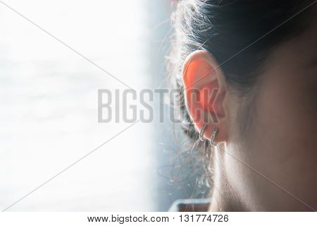 Close up ear of woman with sunlight background.
