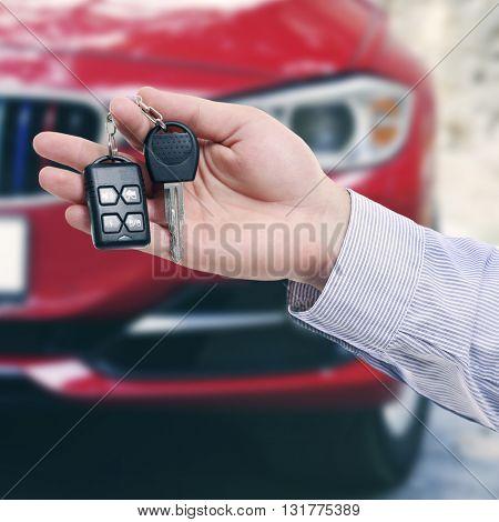 Male hand holding car keys on car background