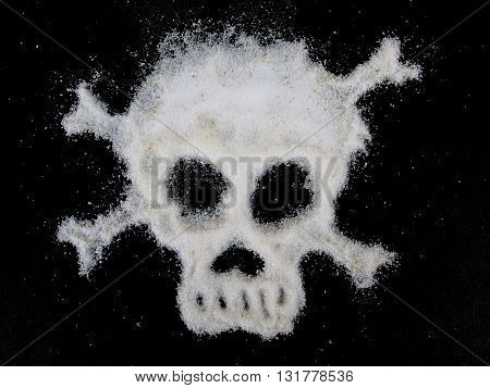 Sugar can be deadly: Skull shaped from white sugar on black background: relates to diabetes, heart disease, obesity.