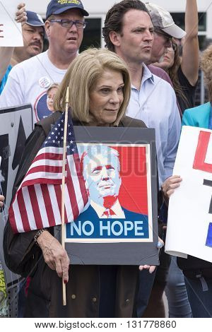 SAN DIEGO USA - MAY 27 2016: A woman peacefully protests Donald Trump's presidential campaign by holding an American flag with a