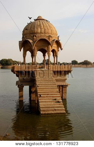 Arched domed and decorative canopy on stone platform at Gadisar Lake Jaisalmer Rajasthan India Asia
