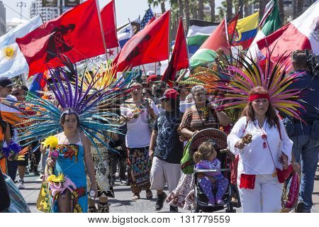 SAN DIEGO USA - MAY 27 2016: Latinos celebrate their culture as women protesters march in traditional Aztec attire followed by a large crowd and flags representing Latin American countries outside a Trump rally in San Diego.