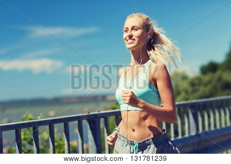 fitness, sport, people, music and healthy lifestyle concept - smiling young woman with earphones running outdoors