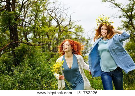 Best friends forever. Girlfriends have fun walk in the park. BFF. A girl holding a bouquet of wildflowers. A wreath of flowers at the girl on the head.
