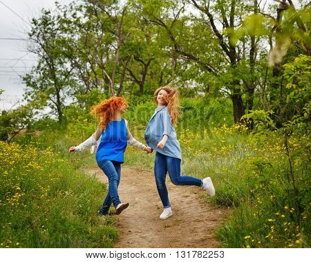 Best friends forever. Girlfriends whirl on the footpath in the park. BFF. Close friends. Gentle friendship. Fooling around together.