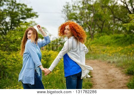 Best friends forever. Girlfriends strolling hand in hand in the park. BFF. Close friends. Gentle friendship.
