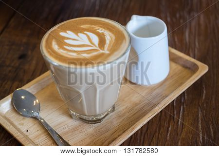 A glass of hot Piccolo latte coffee in wood tray on wooden table in cafe.