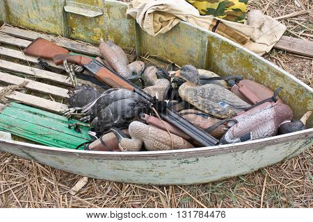 Hunting boat with a hunting rifle and stuffed ducks