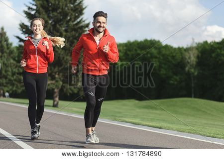 Happy sport man and woman jogging in green park along long road. Photo of happy couple running outdoors.