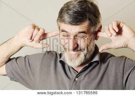I can not hear you! Close up portrait of a senior man with his fingers in ears