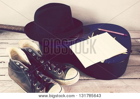 Vintage tone:guitar hat sneakers Book Pencil on wood table