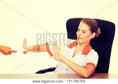 Young woman doctor refusing bribe