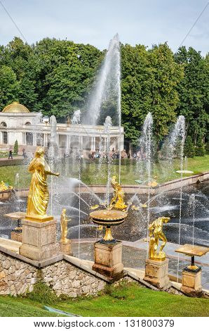 Petergof St Petersburg Russia - September 1 2012: Golden statues at fountains of Grans Cascade at Grand Petergof Palace. Unidentified tourists present on picture.