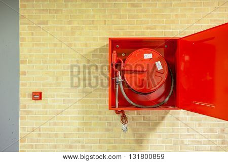in the hallway of a nice building there is an fire hose