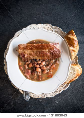 Cooked beans with ribs on rustic background