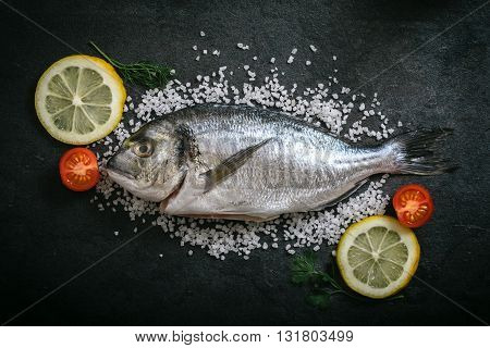 Gilthead fish and ingredients on rustic background