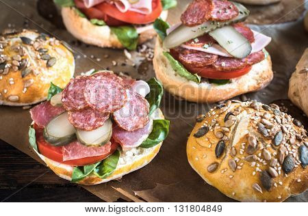Photos of sausage sandwiches on rustic background